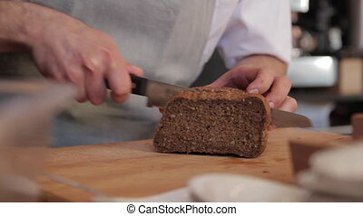 cook cuts a slice of bread