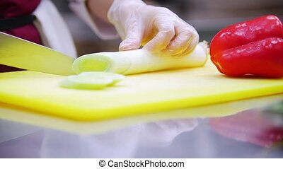 Cook cuts asparagus on a yellow board, which is next to the red pepper