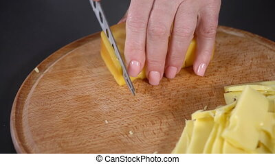 Cook cuts hard cheese - Chef cuts hard cheese on a cutting...