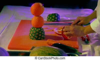 Cook cuts orange slices for fruit statuette on competition
