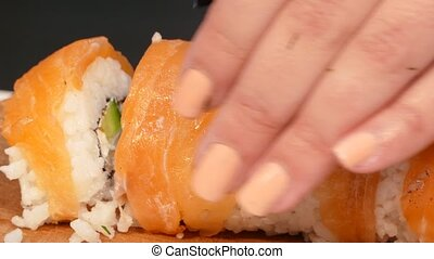 Cook cuts sushi roll covered with salmon meat - The cook...