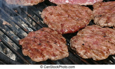 Cook grilling, turning hamburgers