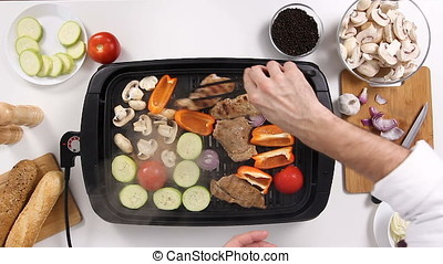 Cook hands turning the meat on the grill alongside to vegetables