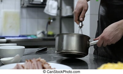 Cook hands whipping cream and eggs in a pan