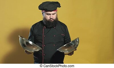 cook in a black suit on a yellow background - cheerful cook...