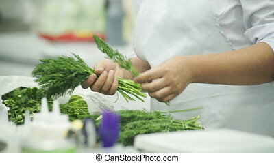 Cook in a white apron, choose a good dill and gathers in her hand.