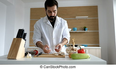 Cook in modern kitchen putting cut mushrooms in a bowl