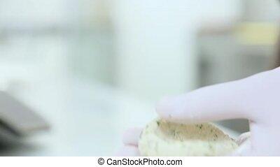 Cook in white gloves makes snacks