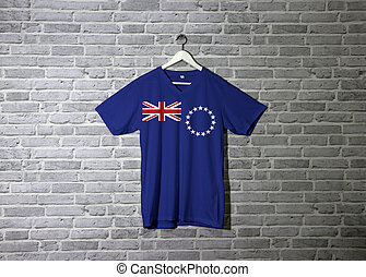 Cook Islands flag on shirt and hanging on the wall with brick pattern wallpaper.