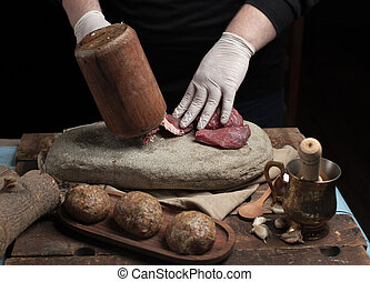 Cook makes meal meat with dark background