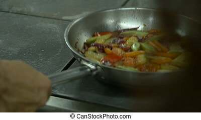 Cook mixing the vegetables frying by throwing it in the air in the kitchen,