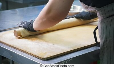 Cook on commercial kitchen in restaurant prepares dough for ...