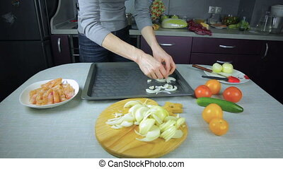 Cook onion lays on a baking sheet - Cook chef put onion lays...