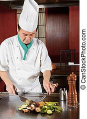 Cook prepares fried vegetable dish - Oriental cuisine. ...