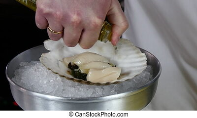 Cook prepares sea salad of scallops on shell.