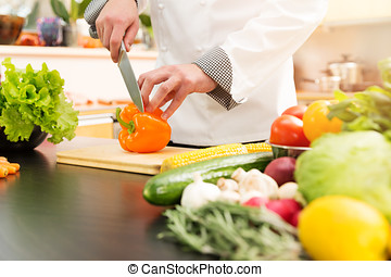 cook preparing vegetable salad in domestic kitchen