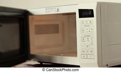 A cook inserts a food bowl for heating in the microwave oven. Sound included if needed it. A microwave oven, often colloquially shortened to microwave, is a kitchen appliance that heats food by bombarding it with electromagnetic radiation in the microwave spectrum causing polarized molecules in the ...