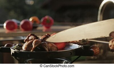 Cook puts hot meat from the grill on the tray with...