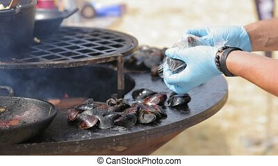Cook puts mussels on the barbecue plate at the street...