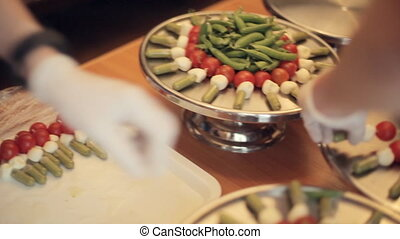Cook puts on a large tray canapes from tomatoes, mozzarella and sauce, in the center of the tray pea pods