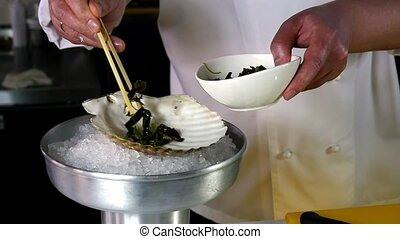 Cook puts seaweed on a shell in the restaurant.