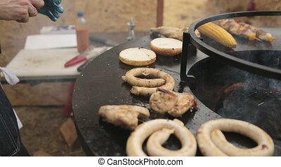 Cook roasts burger buns and meat on the large round grill...