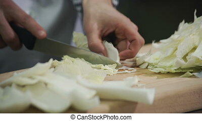 Cook separates the leaves from the stalks of Chinese cabbage.