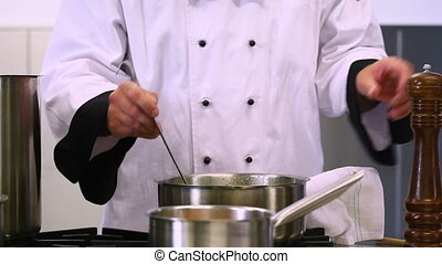 Cook stirring and flavoring soup in professional kitchen
