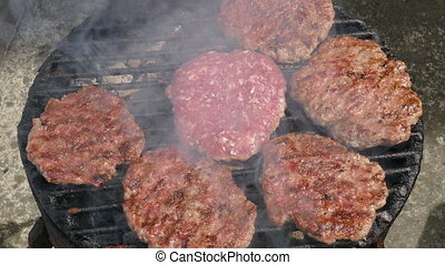 Cook turning hamburgers, barbecue