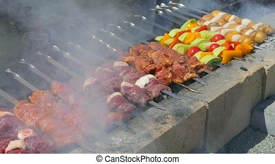 Cook turns vegetables and meat on skewers