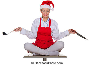 Cook with dishes in the cap of Santa Claus