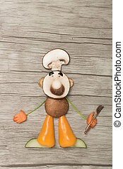 Cook with fork made of vegetables on wooden background