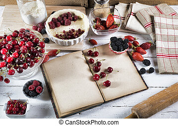 cookbook with ingredients and red fruits
