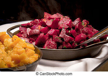 Cooked beets and sweet potatoes on a buffet table