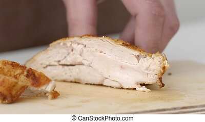 Cooked chicken breast is re-bred into pieces on a wooden board in slow motion