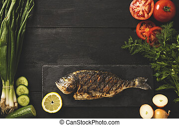 Cooked dorado fish on a black stone