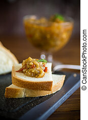 cooked eggplant caviar with spices on a wooden table