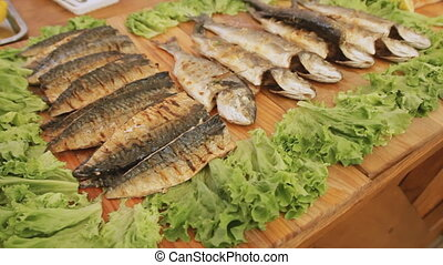 Cooked fish with salad on the table at the street food...