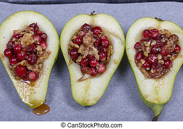 Cooked for baking in the oven pears with honey, cranberries and walnuts, top view