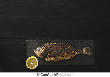 Cooked fresh bream or dorado fish on a black stone with a slice of lemon