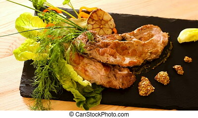 Cooked fried pork meat with different herbs served on black ...