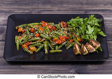 Cooked green beans, red cherry tomato with sesame seeds in black plate
