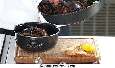 Cooked mussels in a pot. Seafood, toasts and lemon.
