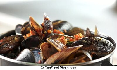 Cooked mussels macro. Clams with vegetables and rosemary.
