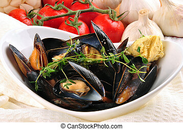 Cooked mussels with garlic butter sauce and thyme in a white bowl