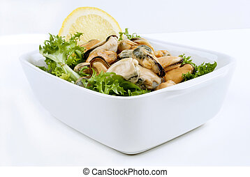 Cooked mussels with lemon on fresh salad in a white bowl