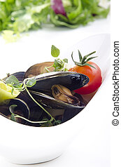 Cooked mussels with tomato in a white bowl