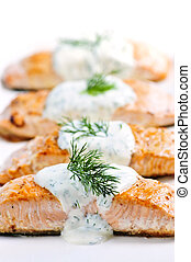 Cooked salmon fillets with dill sauce on white plate