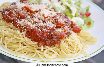 Cooked spaghetti pasta topped with a delicious homemade meat sauce and freshly grated Parmesan cheese and a fresh garden side salad topped with creamy Ranch dressing