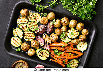 Cooked vegetables on baking tray over dark background....
